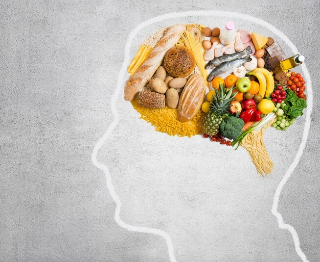 Human head shape with variety of different food ingredients on gray background