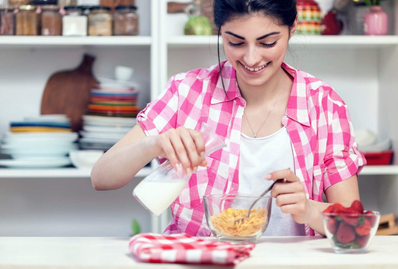 Young Beautiful Girl Preparing Cornflakes for the Breakfast In Kitchen